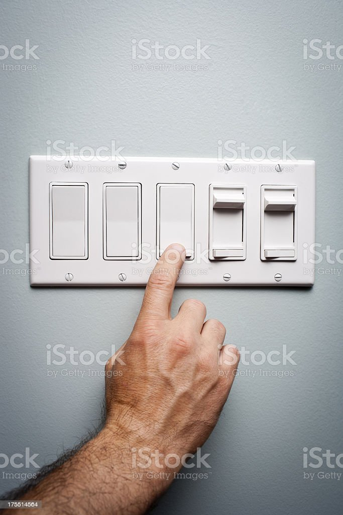 Man turns off a Light Switch stock photo