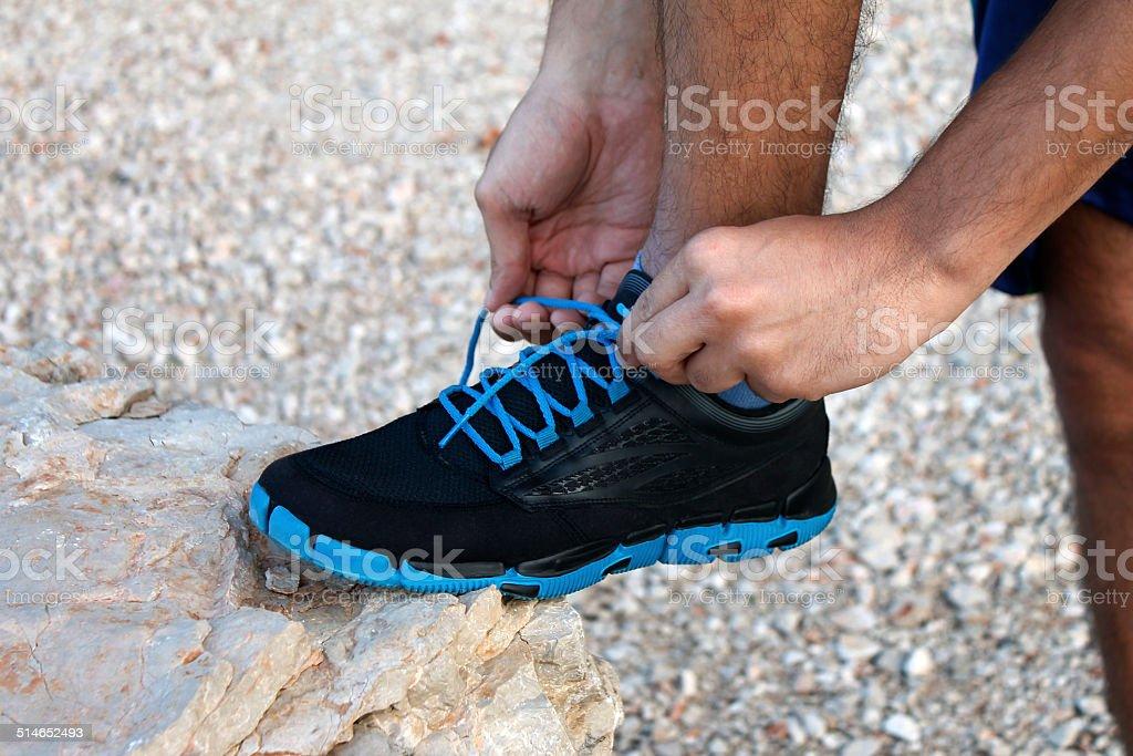 Man tying athletic shoe stock photo