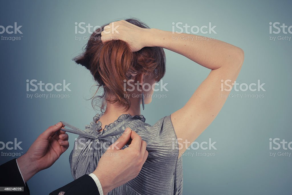 MAn tying bow on woman's dress royalty-free stock photo