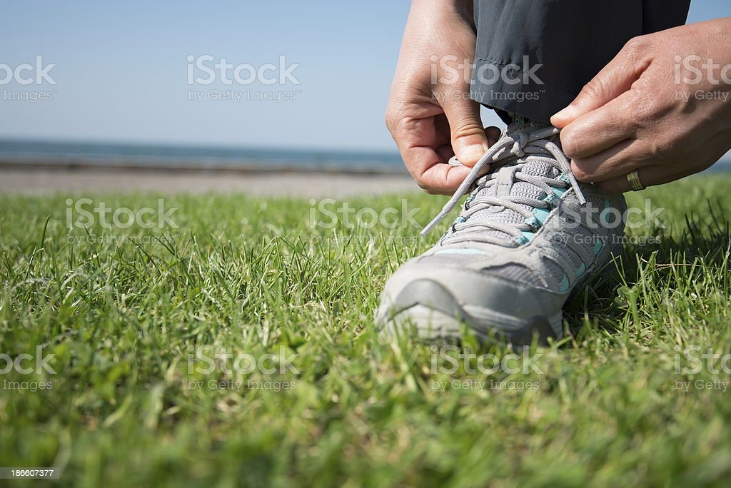 A man tying his sport shoes on the grass stock photo