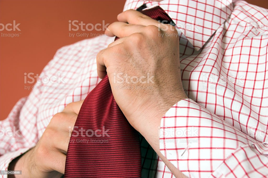 A man tying his tie, getting ready for work stock photo