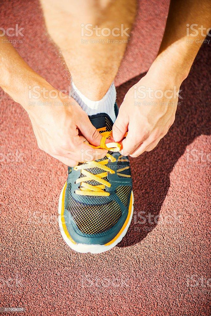 Man tying jogging shoes stock photo