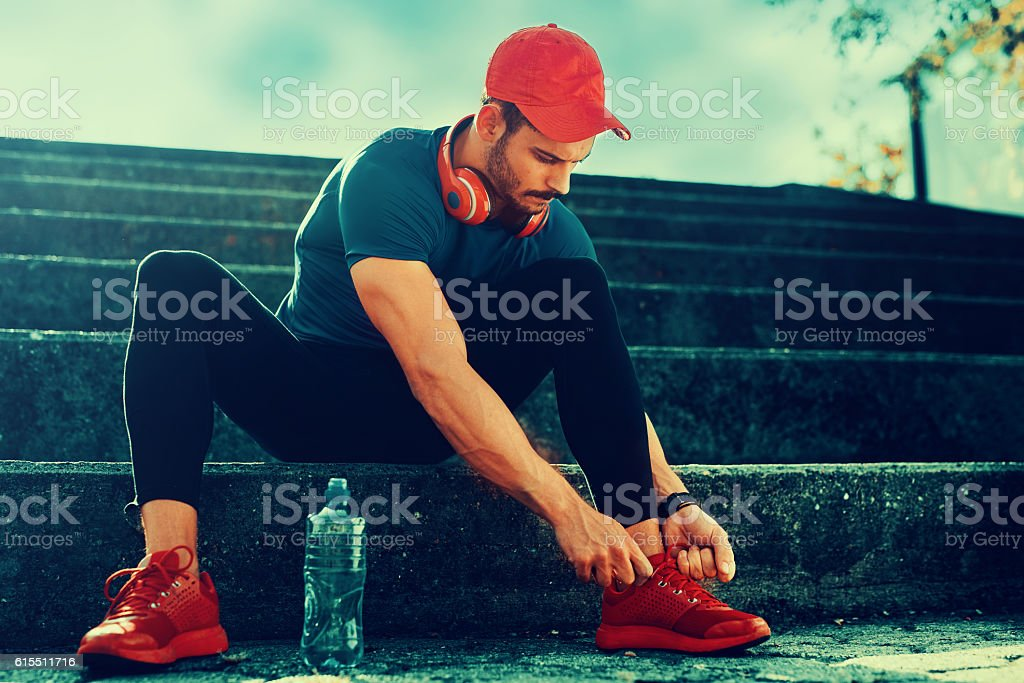 Man tying jogging shoes stock photo