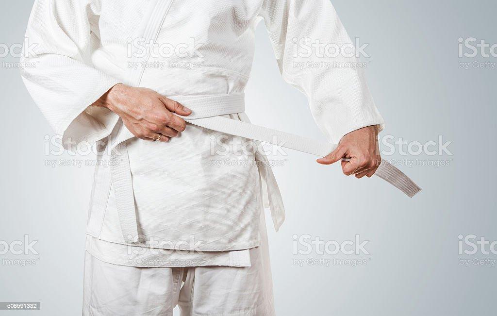 Man tying kimono belt stock photo