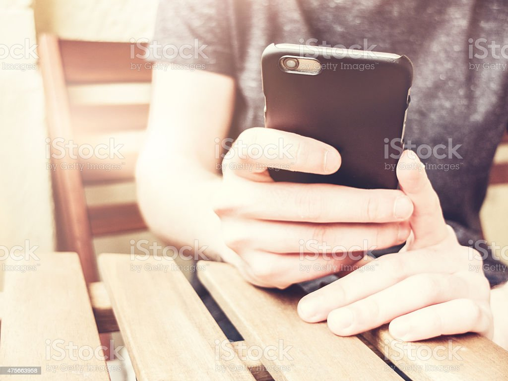 man typing at smartphone stock photo
