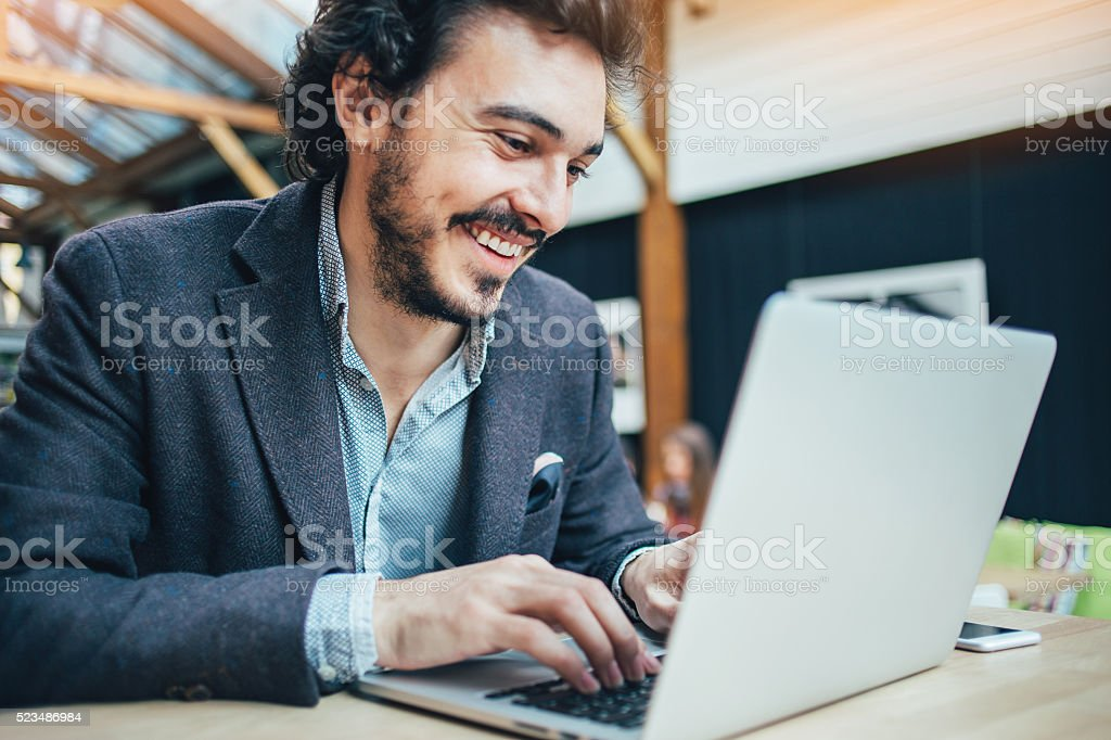 Man typing on a laptop stock photo