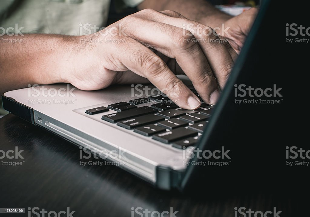 Man typing on an Apple MacBook stock photo