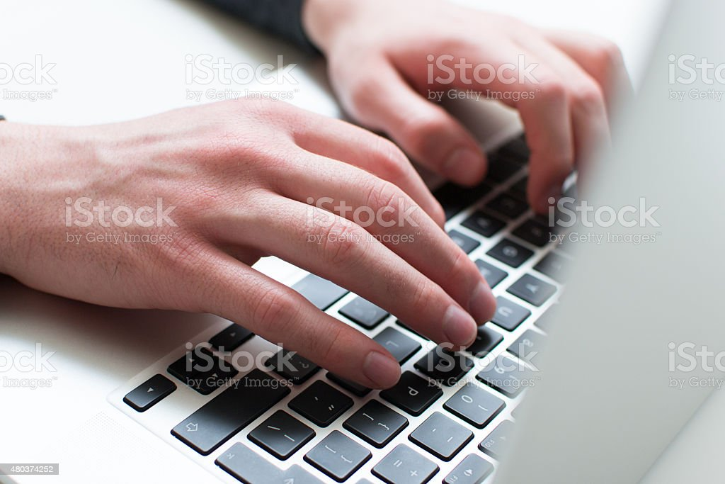 Man typing on his laptop stock photo