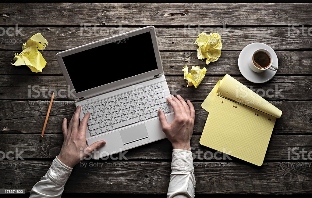 Man typing on laptop with pad of paper and coffee stock photo