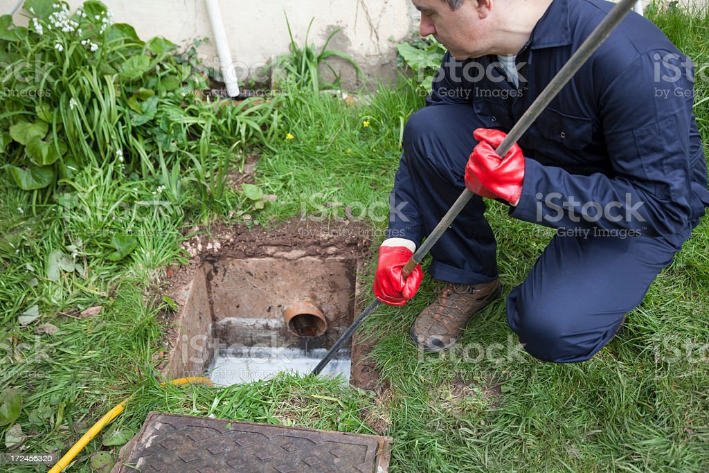 Man unblocking a drain over grass stock photo