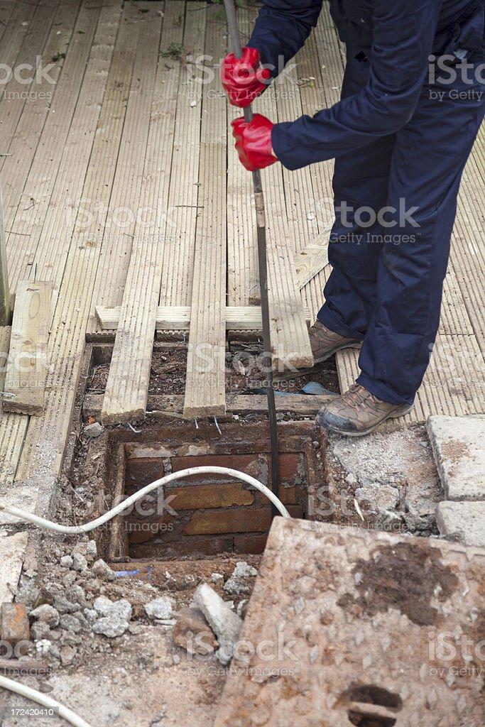 Man unblocking a drain stock photo
