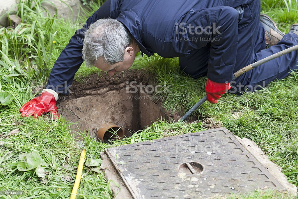 Man unblocking a drain stock photo