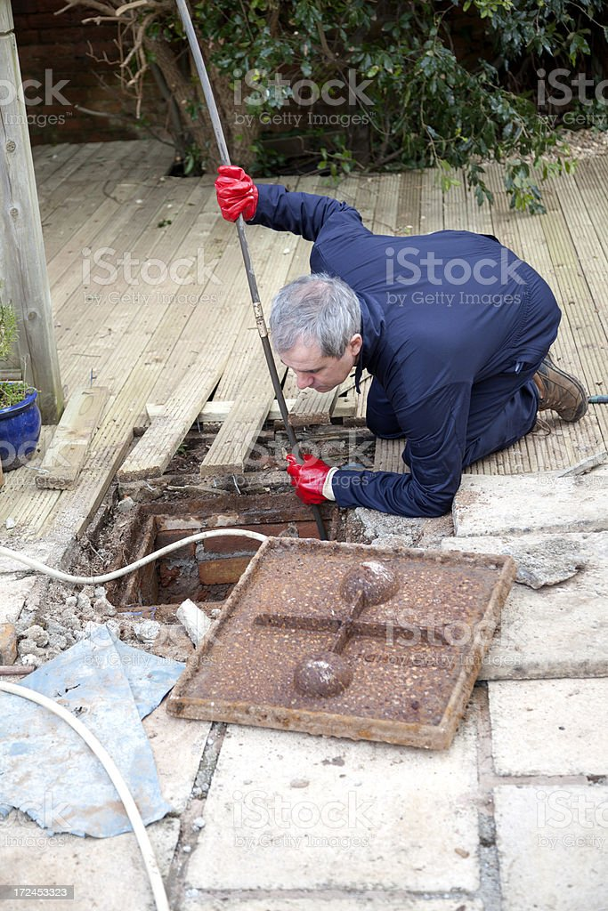 Man unblocking a drain royalty-free stock photo