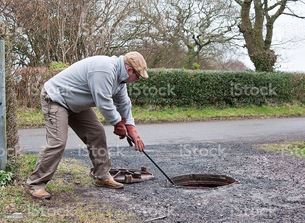 man unblocking drains stock photo