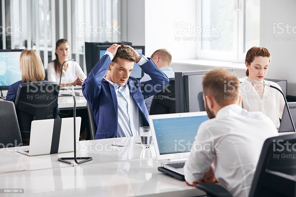 Man under huge dose of stress at work. Corporate business stock photo