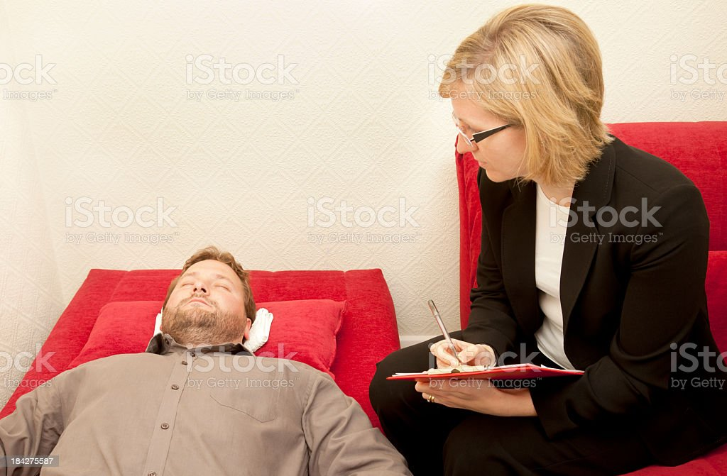 Man undergoing hypnotherapy and a woman surveying him stock photo