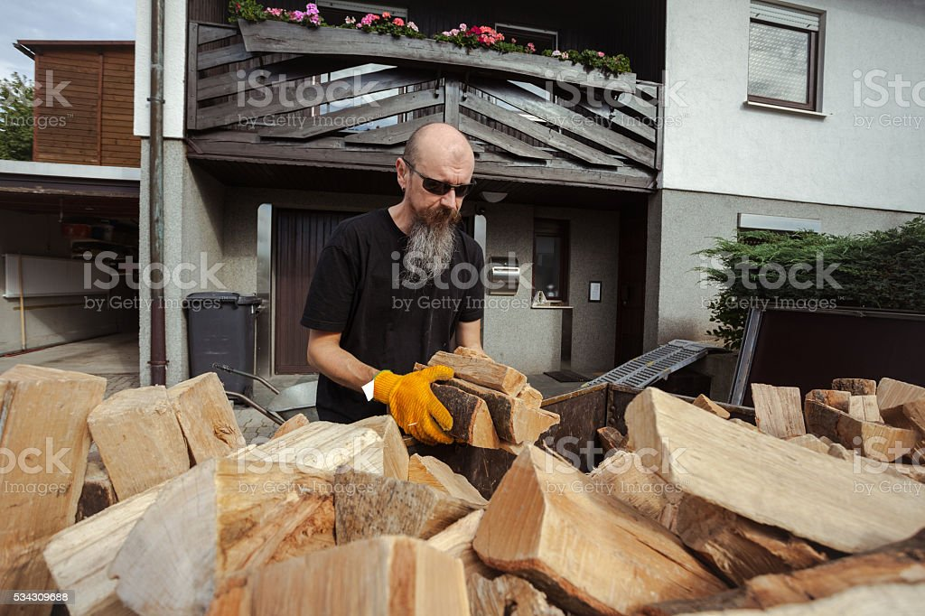Man unloading trailer  loaded with firewood stock photo