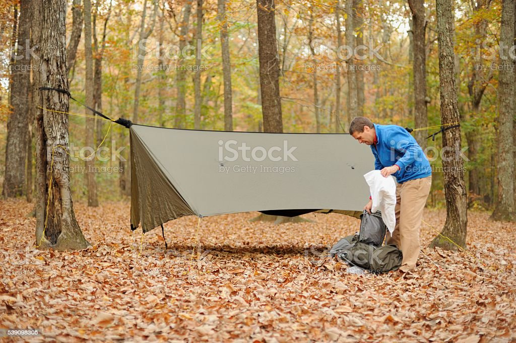 Man unpacking bedding from backpack in campsite stock photo