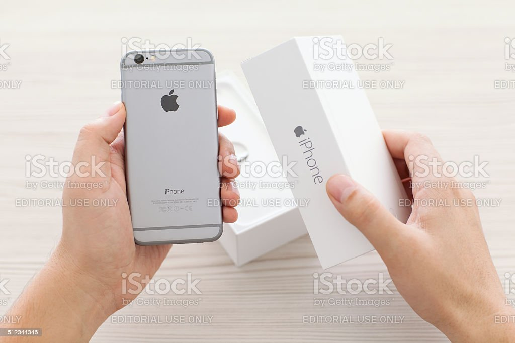 Man unpacking new phone iPhone 6 Space Gray stock photo