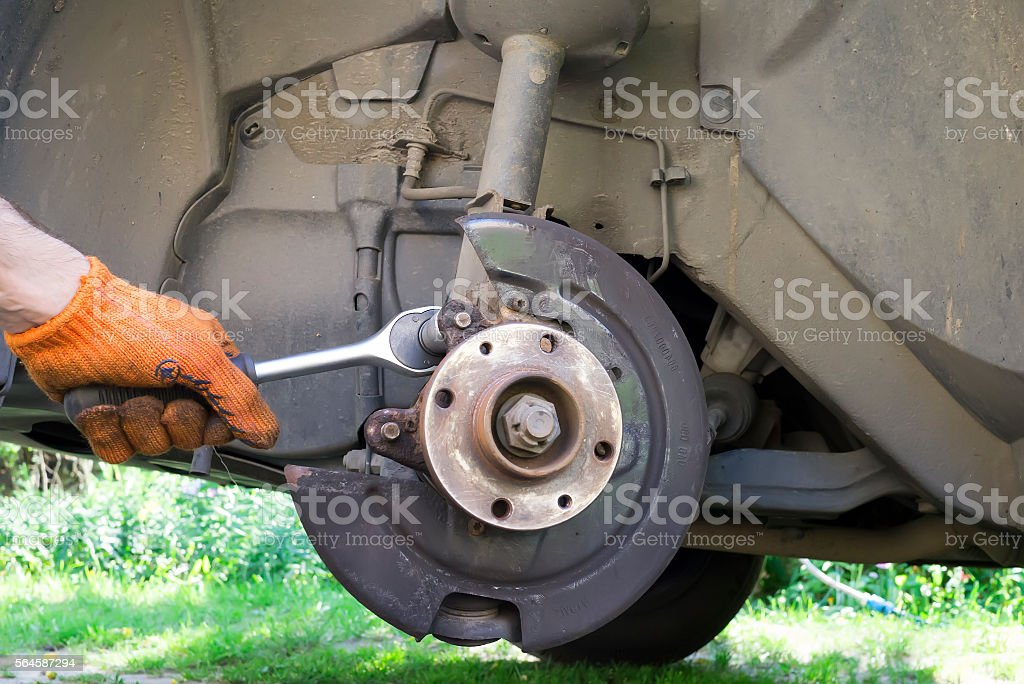 Man unscrew bolt on the brake system of his car stock photo