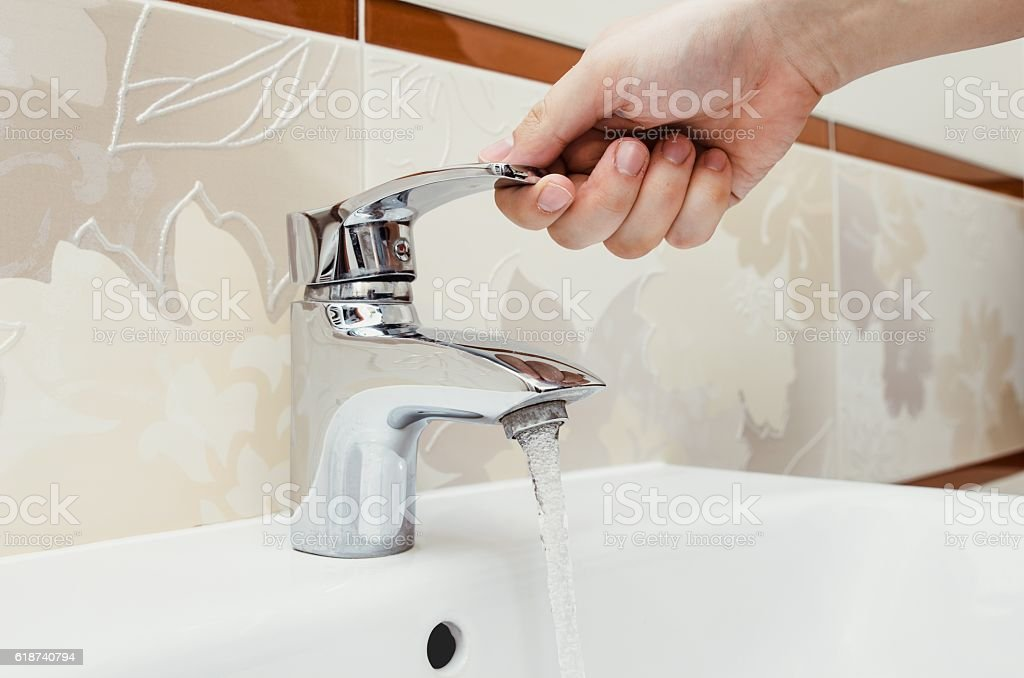 Man unscrew the faucet in the bathroom. stock photo