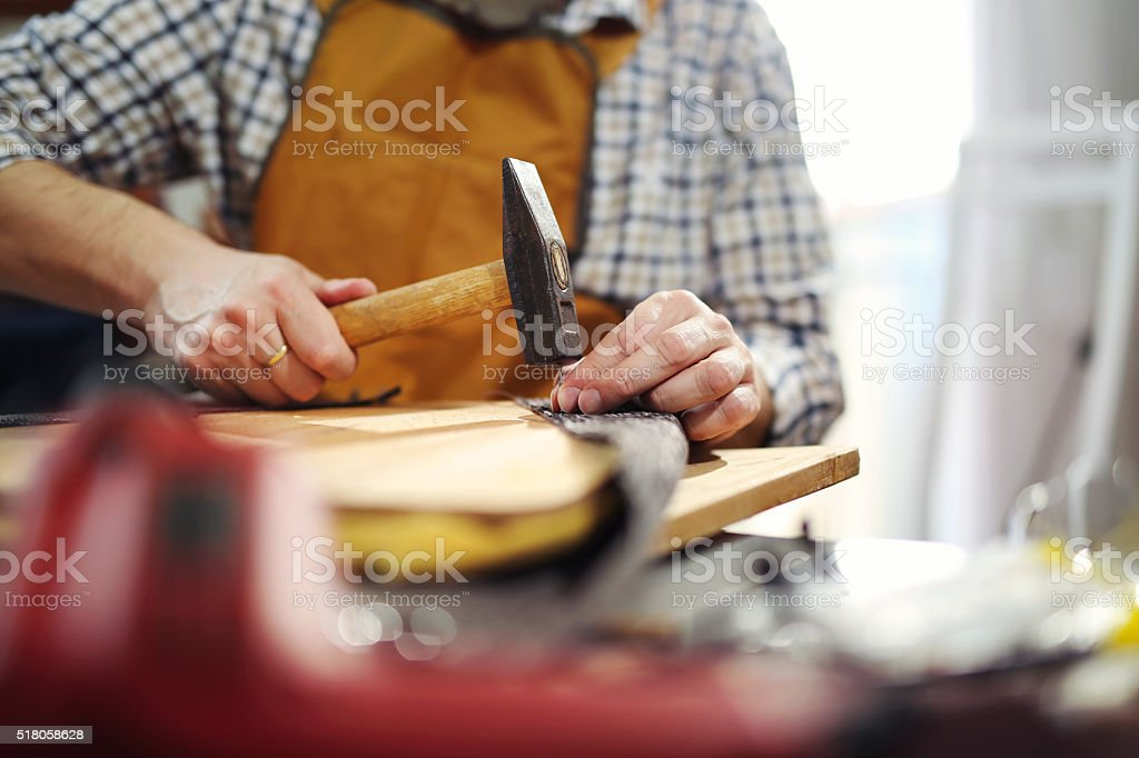 Man upholstering chair in his workshop stock photo
