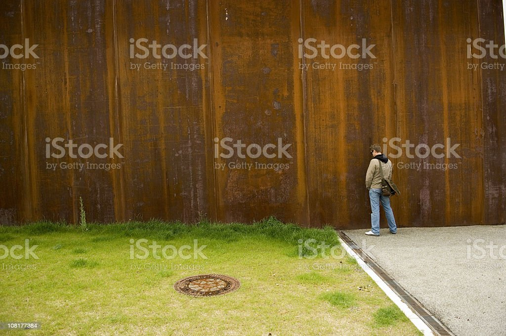 Man Urinating Outside on Rusty Wall Near Green Grass stock photo