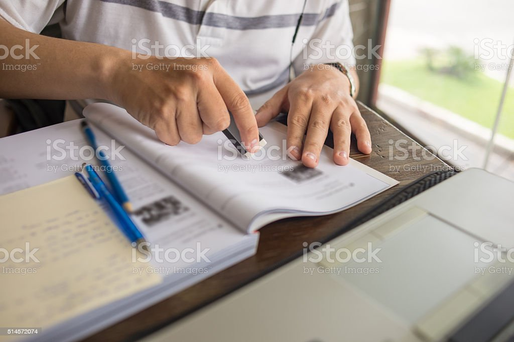 Man use eraser to delete the wrong word on book stock photo