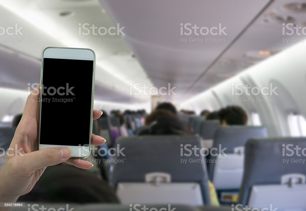 Man use your phone in airplane blurred background stock photo