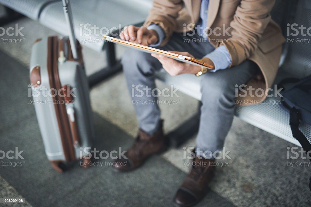 Man uses digital tablet in lounge airport stock photo