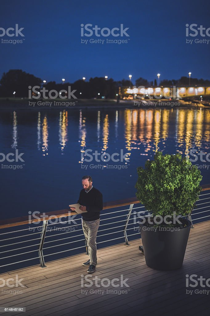 Man uses digital tablet outdoors stock photo