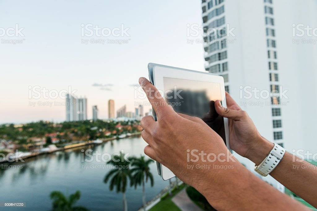 Man Uses Digital Tablet to Take Pictures of Tropical Miami stock photo