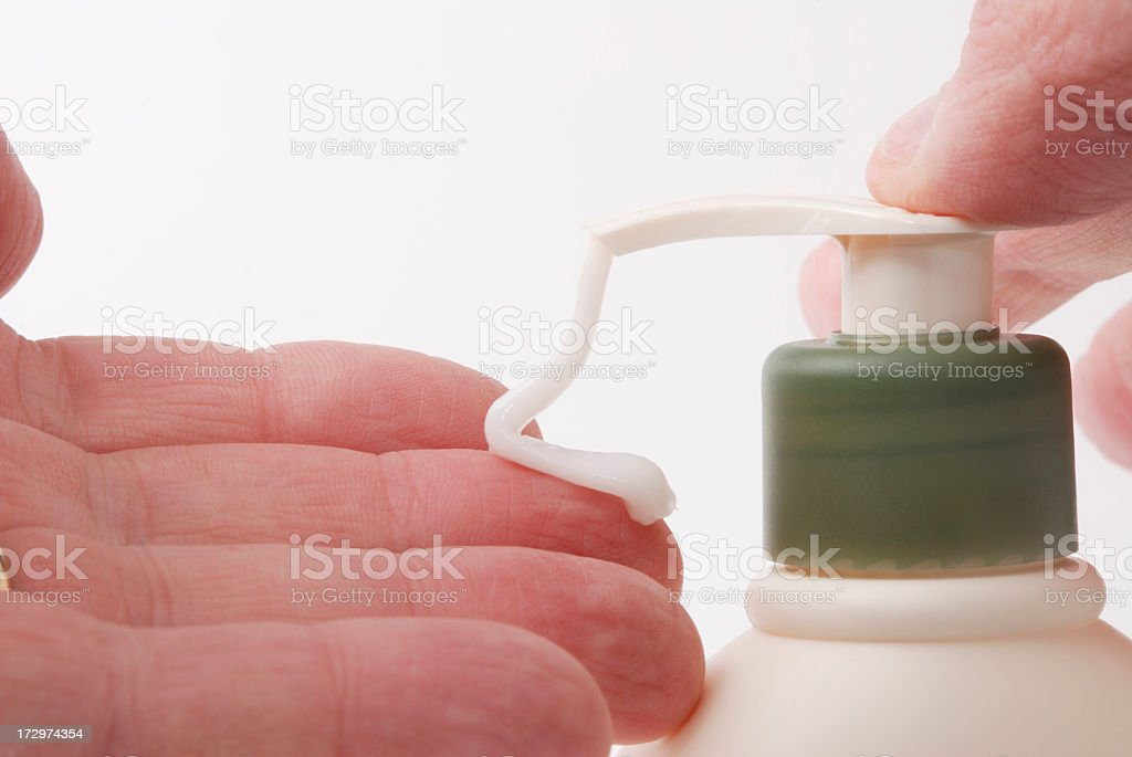 Man uses moisturizer on his dry hands. stock photo
