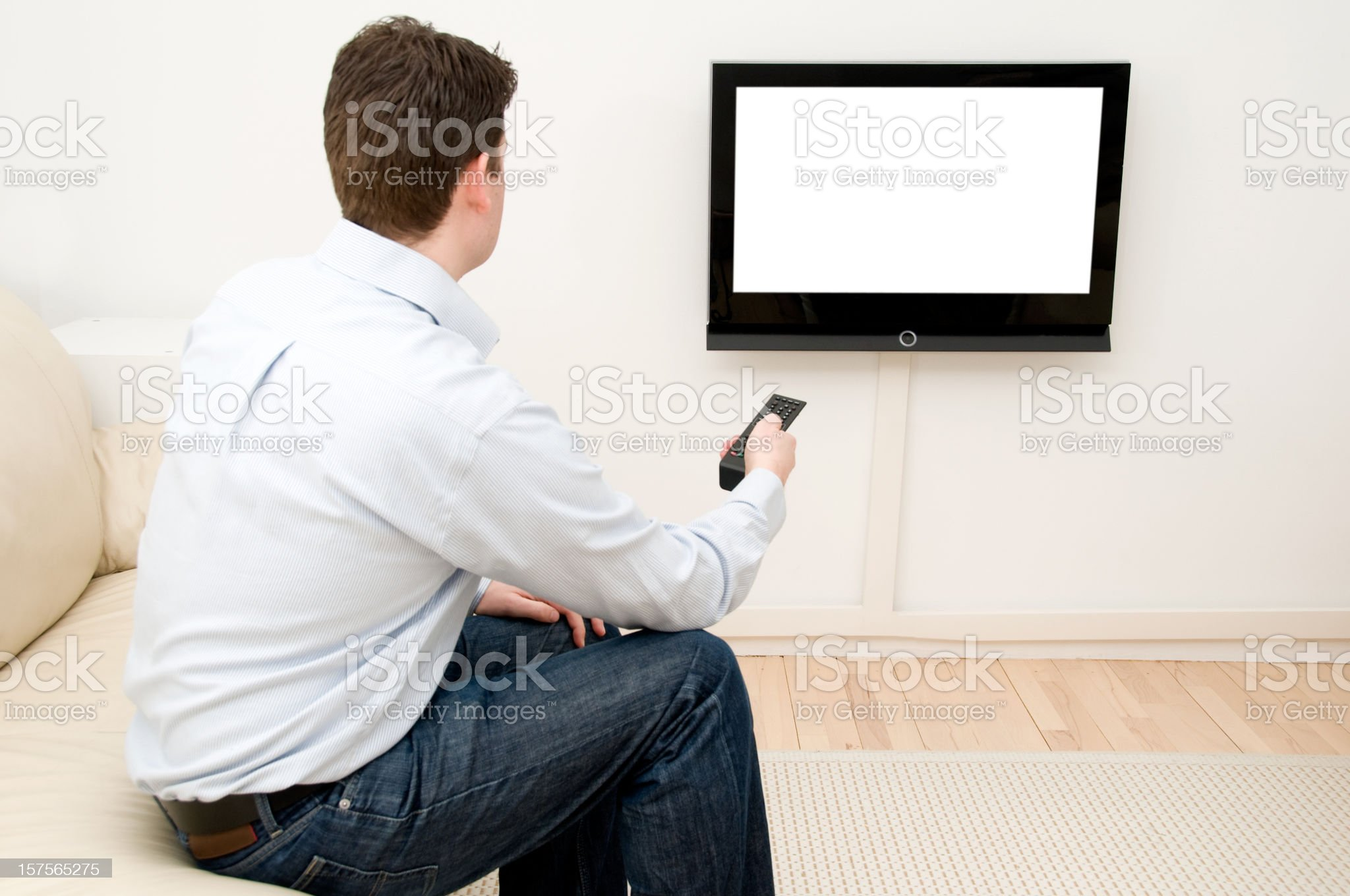 Man uses remote control to change channel on flatscreen tv royalty-free stock photo