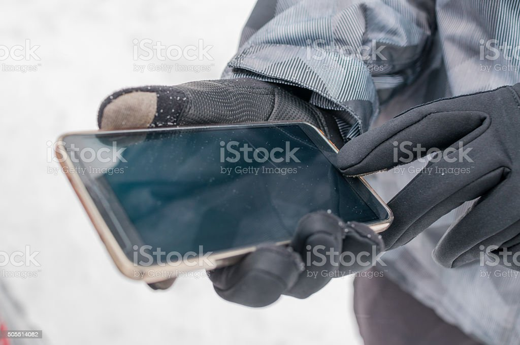 Man uses smart phone in winter stock photo