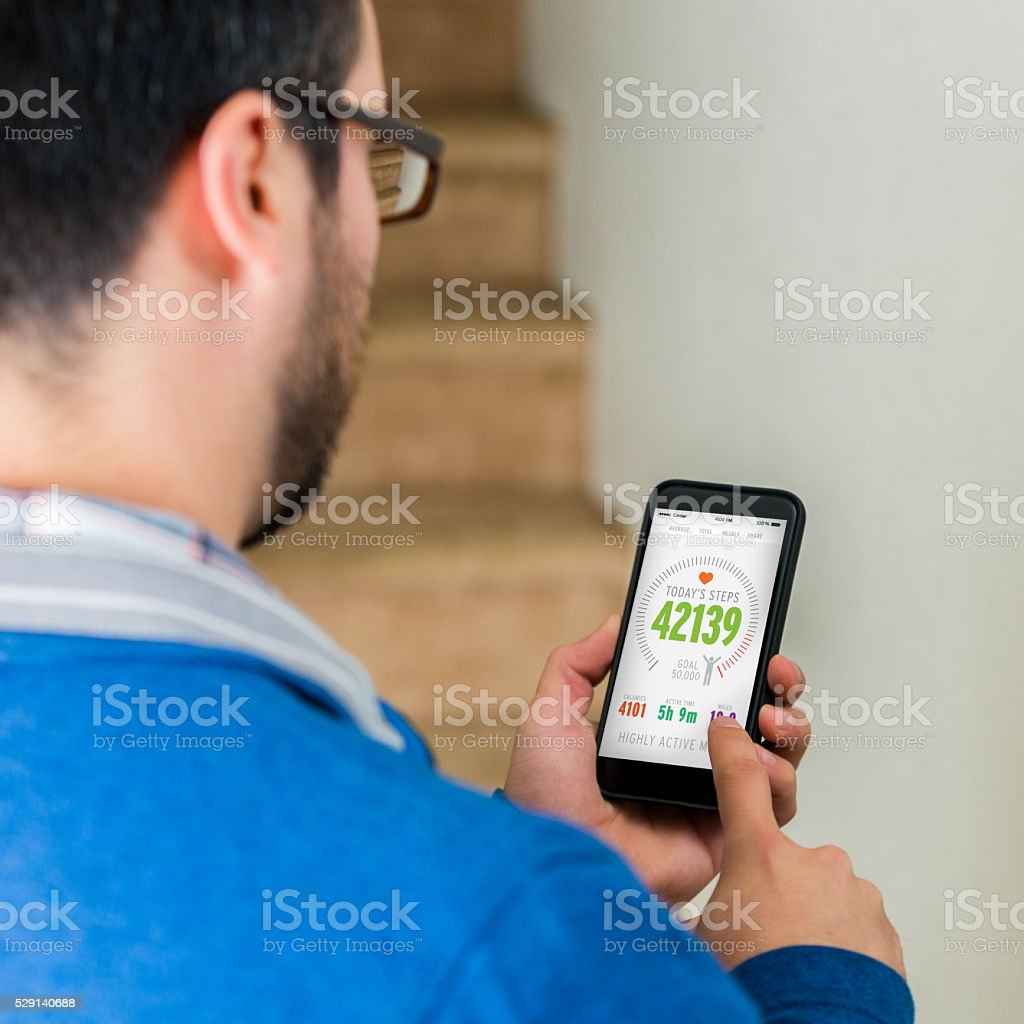 Man uses smart phone technology to assess home security stock photo
