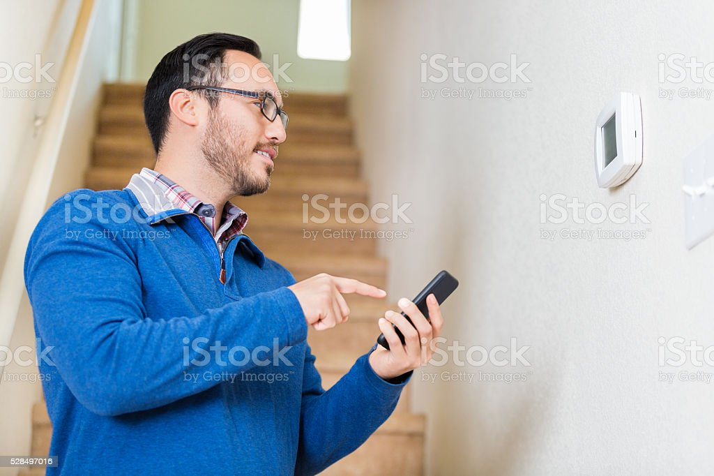Man uses smart phone to control thermostat stock photo