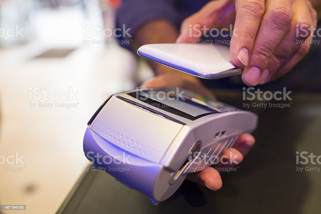 Man uses smart phone to pay with NFC payment technology stock photo