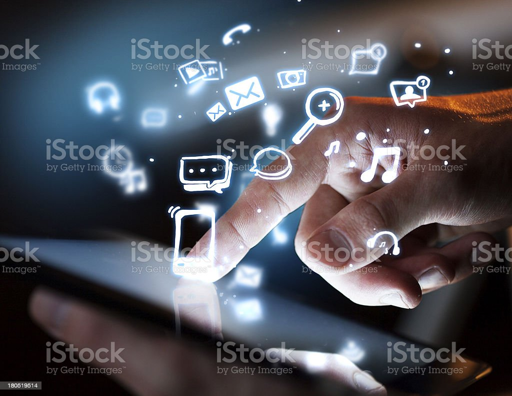 Man uses tablet with floating social media icons stock photo