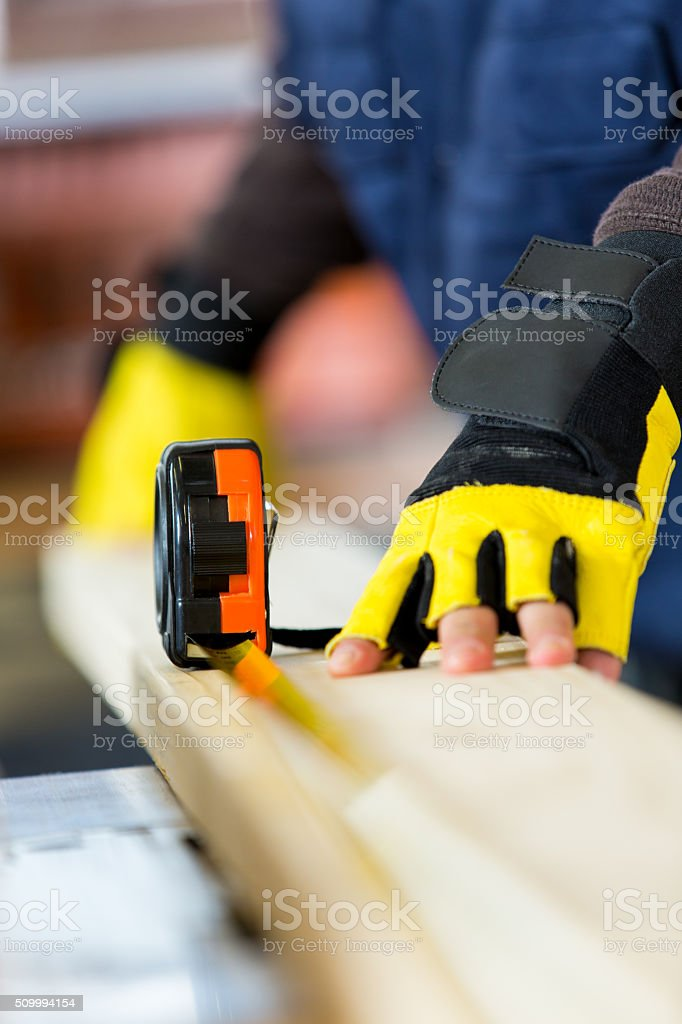 Man uses tape measure in woodworking workshop stock photo