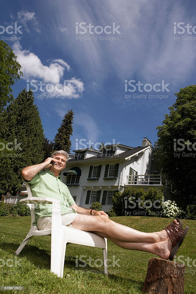 Man using a cell phone in his yard stock photo