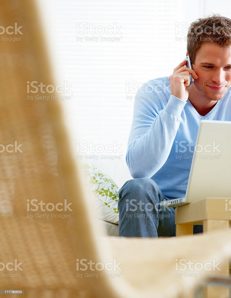 Man using a computer laptop and mobile phone stock photo