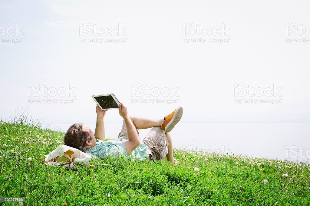 Man using a Digital Tablet Computer outside on a grassy hill royalty-free stock photo
