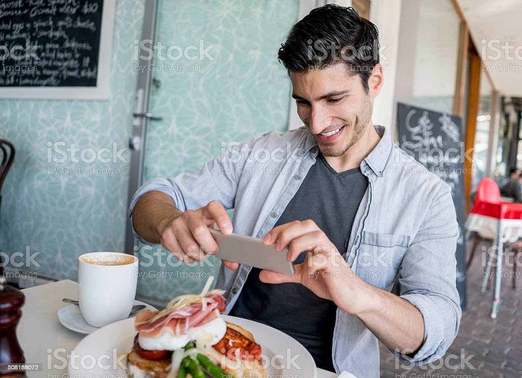 Man using a food app at a restaurant stock photo