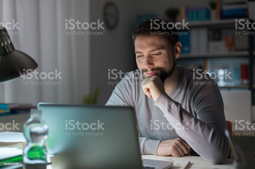 Man using a laptop late at night stock photo