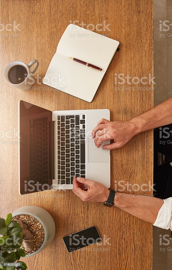 Man using a laptop on wooden table stock photo