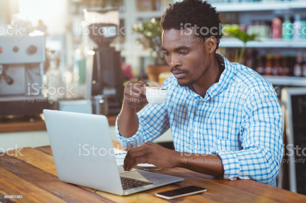 Man using a laptop while having cup of coffee royalty-free stock photo