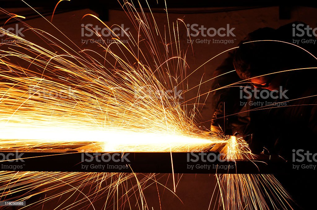 Man using a plasma cutter with sparks flying everywhere stock photo