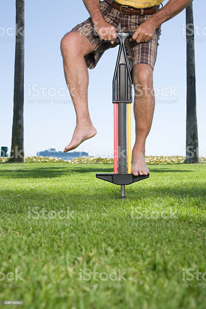 Man using a pogo stick stock photo