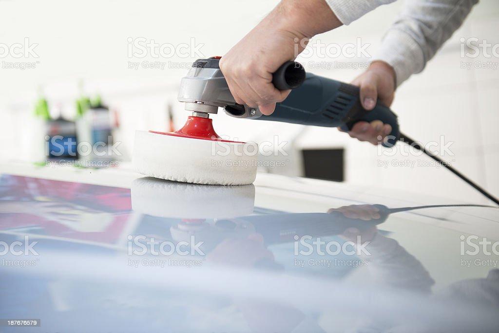 Man using a polishing machine to buff a car stock photo